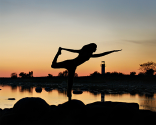 Lady doing Yoga at sunrise.